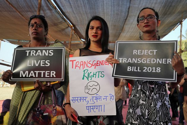 Demonstrators hold placards during a protest against the passing of the Transgender Persons (Protection...