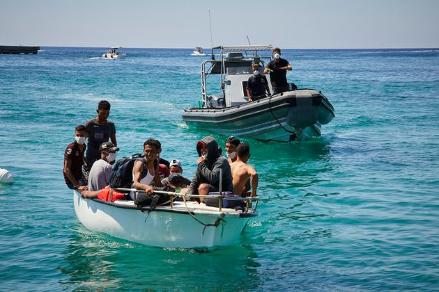 LAMPEDUSA, ITALY - AUGUST 28: Migrants from Tunisia dock their boat at a port on August 28, 2020 in Lampedusa,...