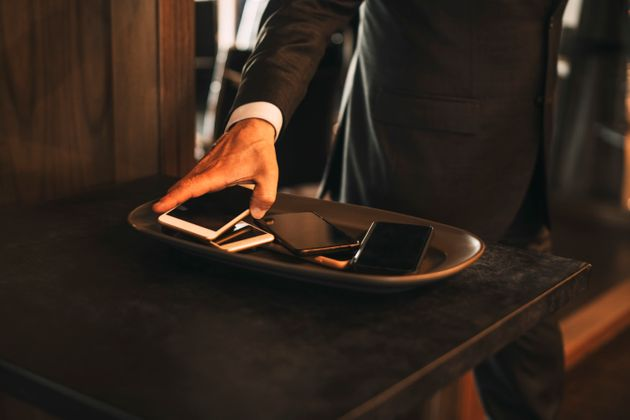 Midsection of male lawyer keeping smart phone on tray at