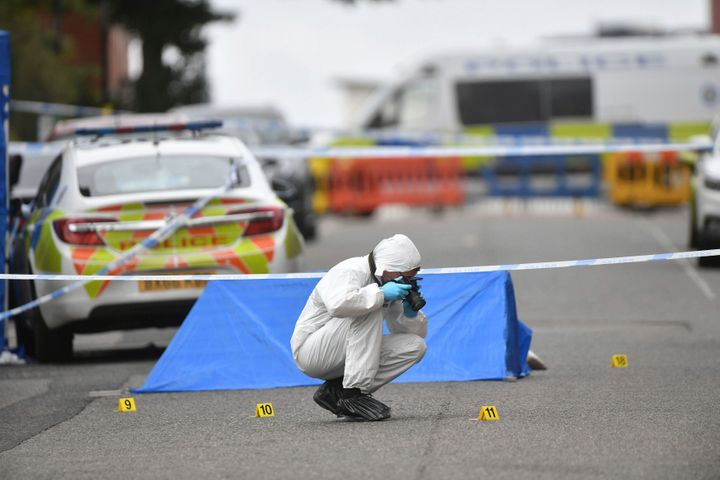 A police forensics officer taking photographs in Irving Street, in Birmingham after a number of people were stabbed in the ci