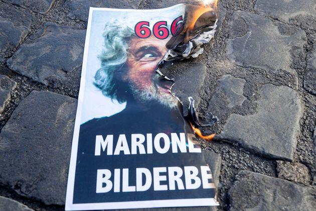 La foto di Beppe Grillo bruciata dai NO