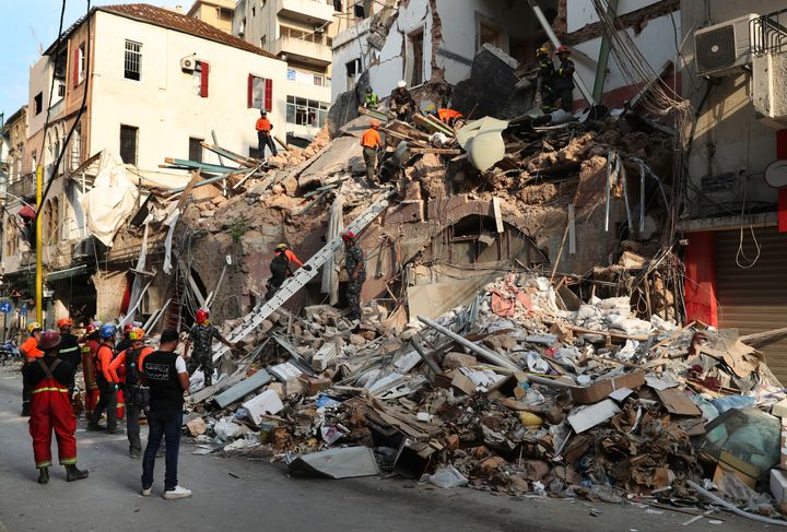 Chilean and Lebanese rescuers search in the rubble of a building that was collapsed in last month's massive explosion, after
