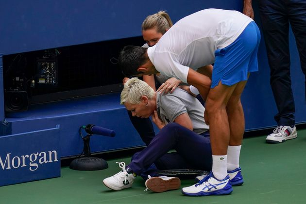 Djokovic checks a the linesman after hitting her with a ball in reaction to losing a point to Pablo Carreno