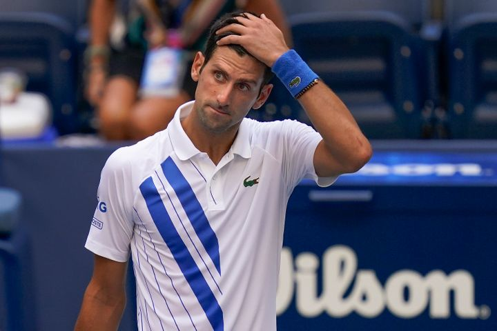 Novak Djokovic, of Serbia, reacts after inadvertently hitting a line judge with a ball after hitting it in reaction to losing