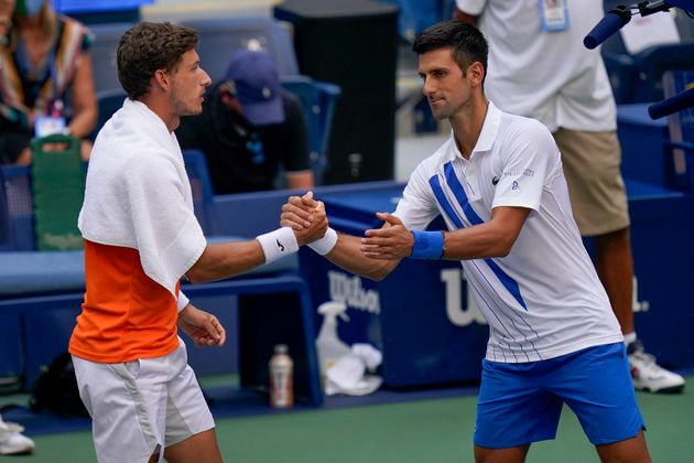 Djokovic shakes hands with Pablo Carreno Busta after defaulting the