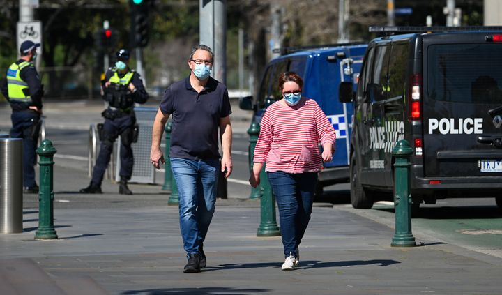 A couple takes a walk as police look on in Melbourne on September 6, 2020 as the state announced an extension to its strict lockdown law while it battles fresh outbreaks of the COVID-19 coronavirus.