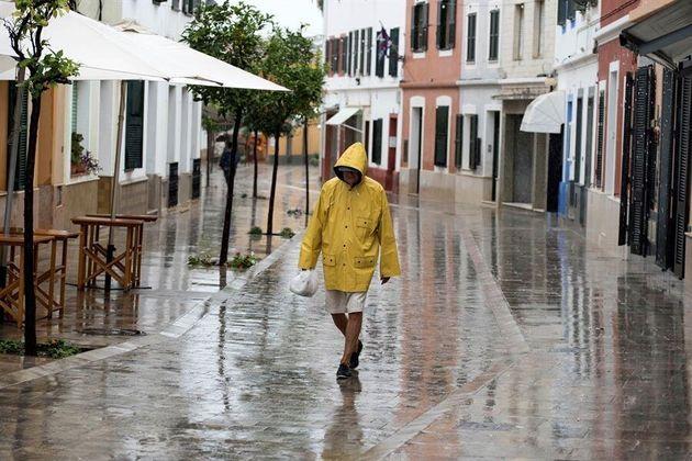 Una persona camina bajo la lluvia por las calle de Es Mercadal, Menorca este