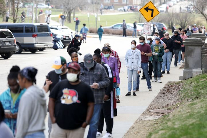 Voters wait in a long line to cast ballots during the presidential primary election held amid the coronavirus outbreak in Mil