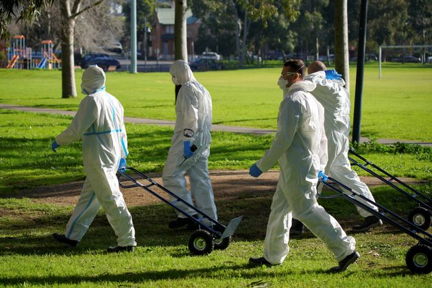 Fire Services Victoria members walk toward a public housing tower, locked down in response to an outbreak...