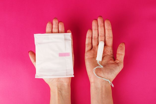 Woman holding menstrual tampon and pad on a pink background. Menstruation time. Hygiene and