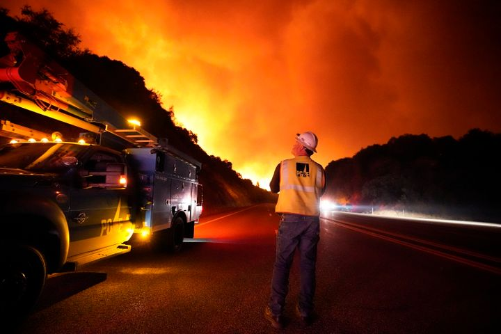 A Pacific Gas and Electric worker looks up at the advancing Creek Fire along Highway 168 Tuesday, Sept. 8, 2020, near Alder S