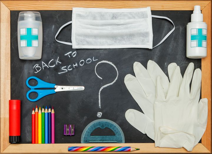 Back to School items and COVID-19 protective equipment on a blackboard. Horizontal composition.