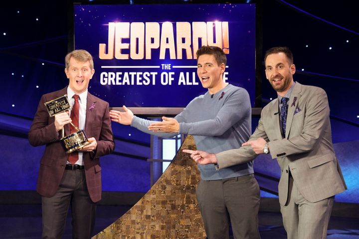 "Ken Jennings holds his ""G.O.A.T."" trophy next to fellow contestants James Holzhauer and Brad Rutter."