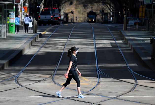 A woman takes a walk in Melbourne on September 6, 2020 as the state announced an extension to its strict...