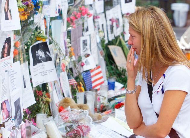 現場近くの追悼広場で、犠牲者の写真を眺める人(ニューヨーク、2001年9月18日)