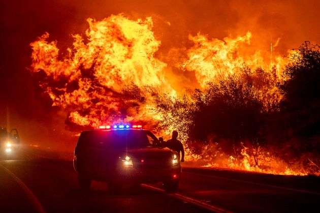 Flames lick above vehicles on Highway 162 as the Bear Fire burns in Oroville, Calif., on Wednesday, Sept....