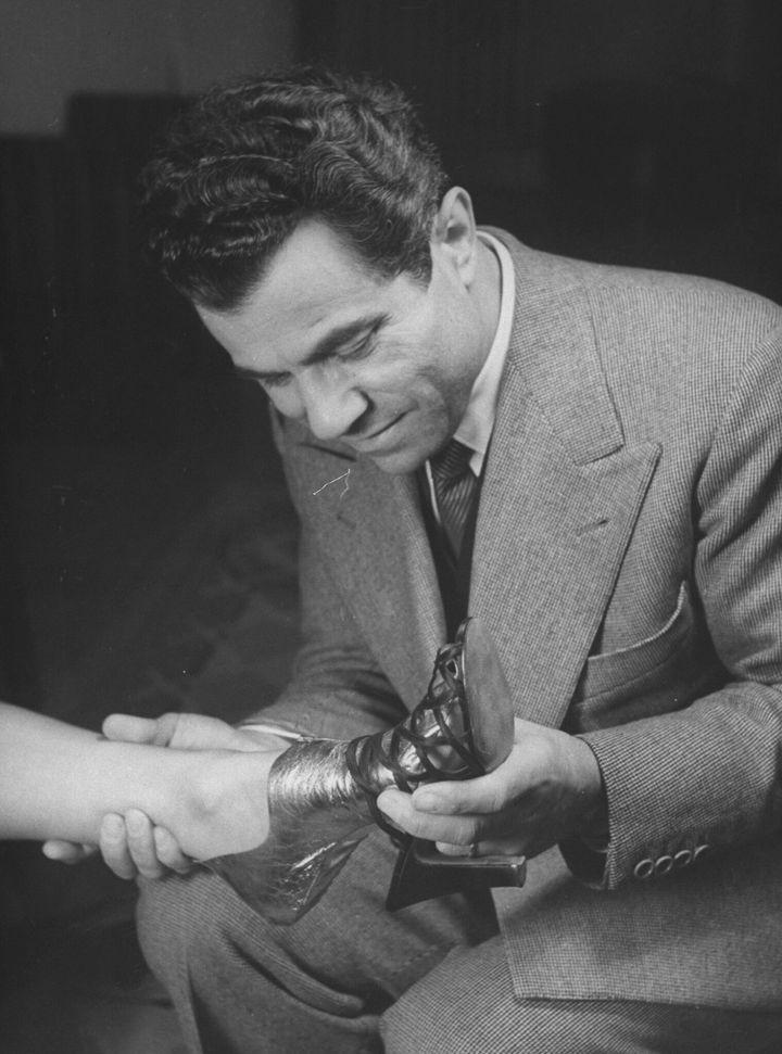 Ο σχεδιαστής Σαλβατόρε Φεραγκάμο δοκιμάζει μια γόβα στο πόδι πελάτισσάς του που το έχει τυλίξει με προστατευτική μεμβράνη.