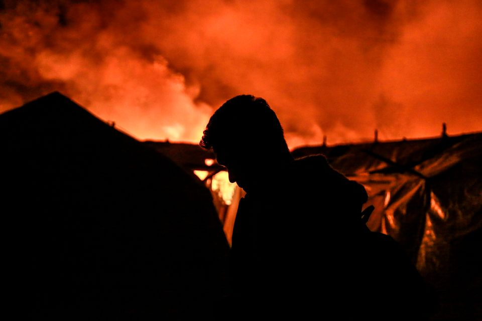 A migrant stands near tents as a fire burns in the Moria camp on the island of Lesbos on September 9,...