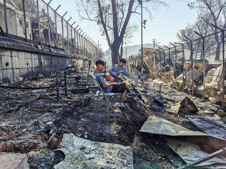 TOPSHOT - Migrants sit inside the burnt Moria Camp on the Greek island of Lesbos on September 9, 2020,...