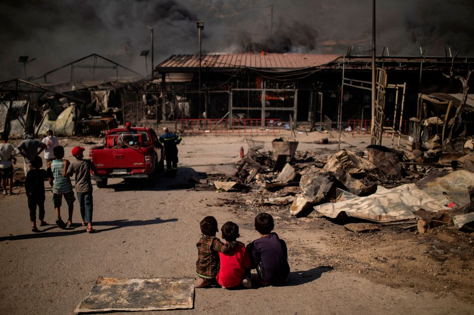 TOPSHOT - Children sit on the ground in the burnt camp of Moria on the island of Lesbos after a major...