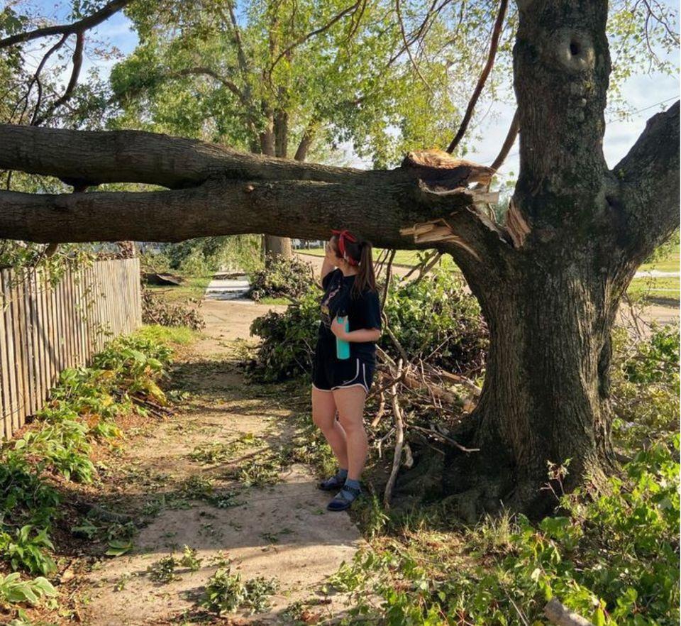 La rédactrice se tient près d'un arbre de son quartier de CedarRapids, dans l'Iowa, durement touché par une tempête de catégorie4. Le phénomène météorologique, un «derecho», a frappé la région au début du mois d'août de cette année.