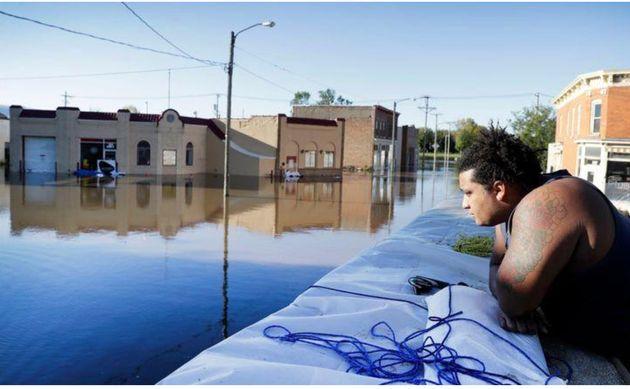 Appuyé sur un mur anti-inondation, CoryHarrison observe les commerces de CedarRapids inondés le 27septembre2016. La ville a érigé en urgence un système de barrières Hesco sur plus de 15kilomètres pour aider à contenir la crue.