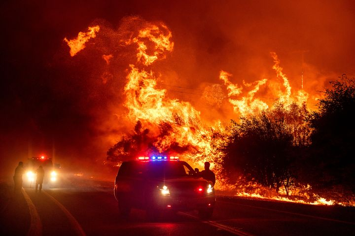 Flames lick above vehicles on Highway 162 as the Bear Fire burns in Oroville, Calif., on Wednesday, Sept. 9, 2020. The blaze,