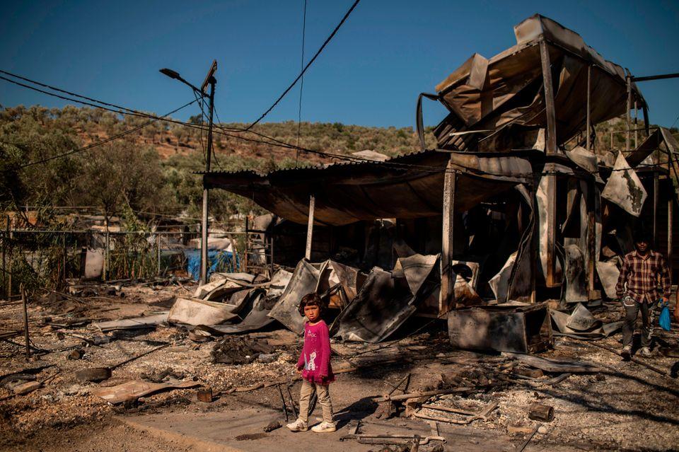 Una niña camina sobre los escombros tras el incendio en