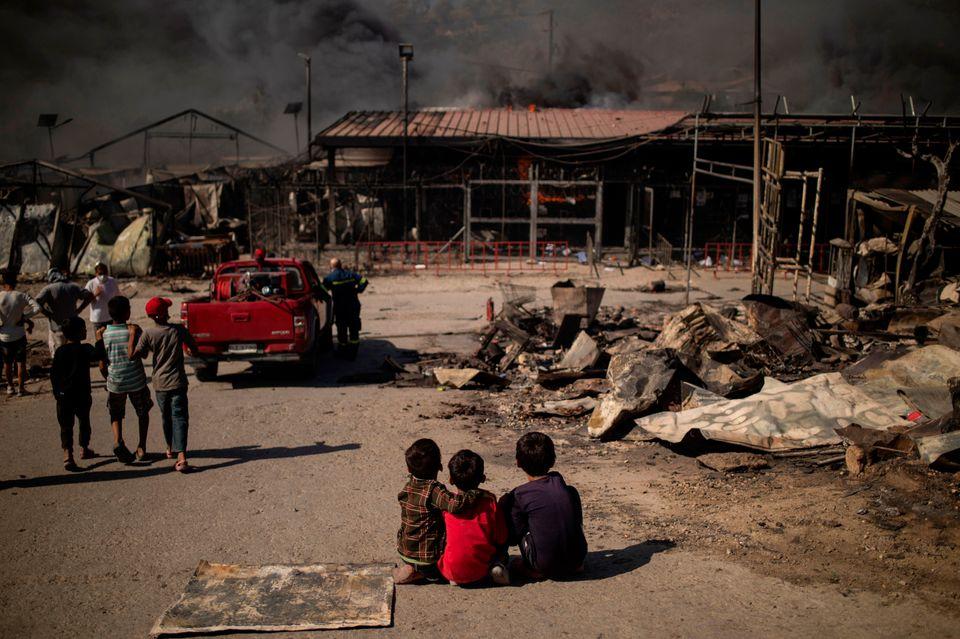 Tres niños observan sentados la devastación del