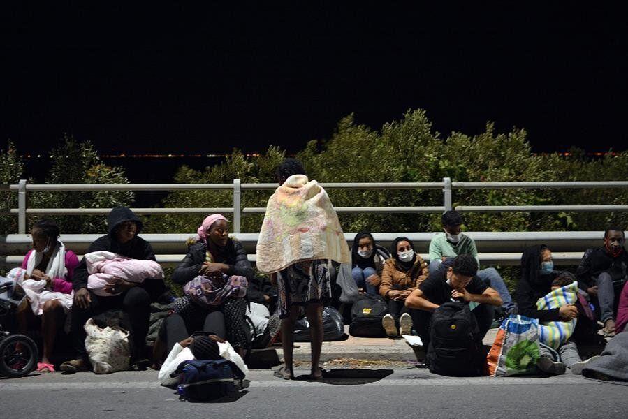 Varias personas sentadas tras haber huido del