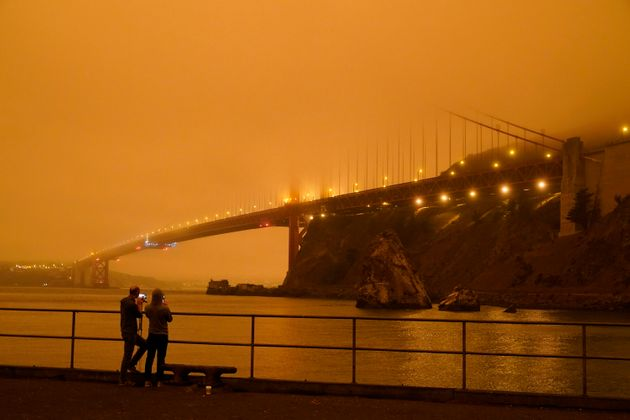 Patrick Kenefick, left, and Dana Williams, record the darkened Golden Gate Bridge covered with smoke...