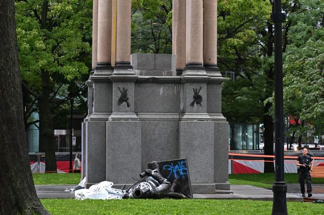 A statue of the first Canadian Prime Minister John A. Macdonald lies on the ground at the base of its...