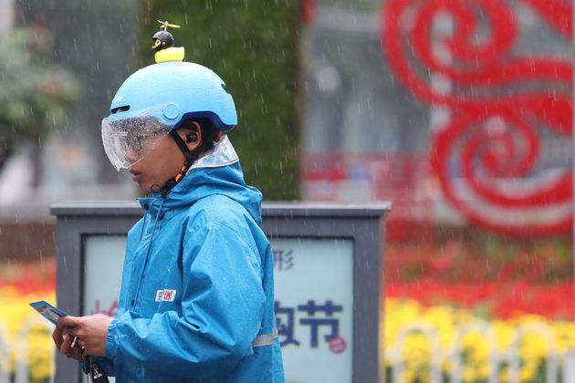 雨の中配送する 餓了麼(ウーラマ)の配送員。青い制服が特徴。餓了麼は中国語で「お腹すいた?」という意味 (Photo by Yang Zheng/VCG via Getty