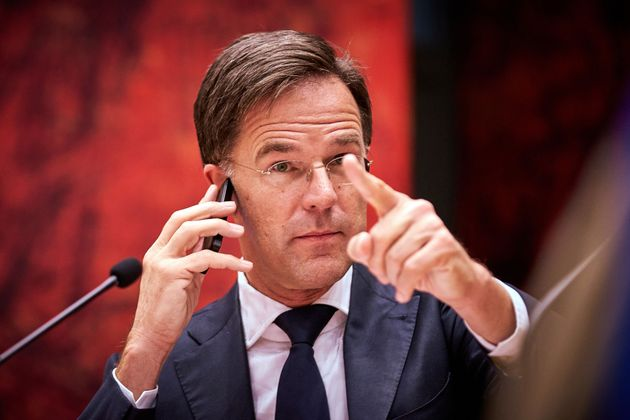 Dutch Prime Minister Mark Rutte gestures as he phones during the debate in the House of Representatives...