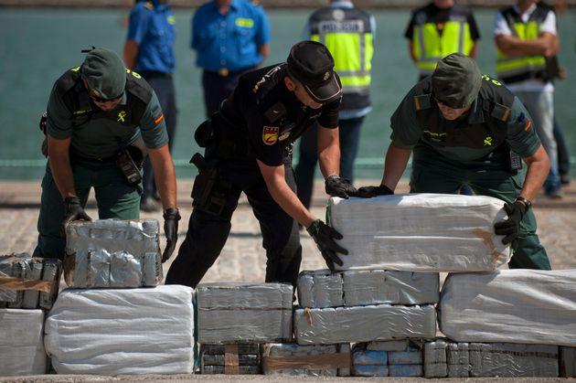 Agentes de la Guardia Civil y de la Policía Nacional, portando parte de un alijo, en el puerto...