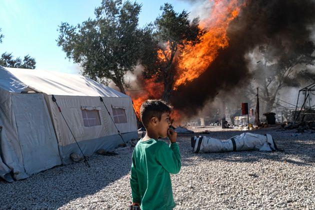 Un niño afgano, refugiado en Moria, mira el fuego en el olivar anexo al campo, esta