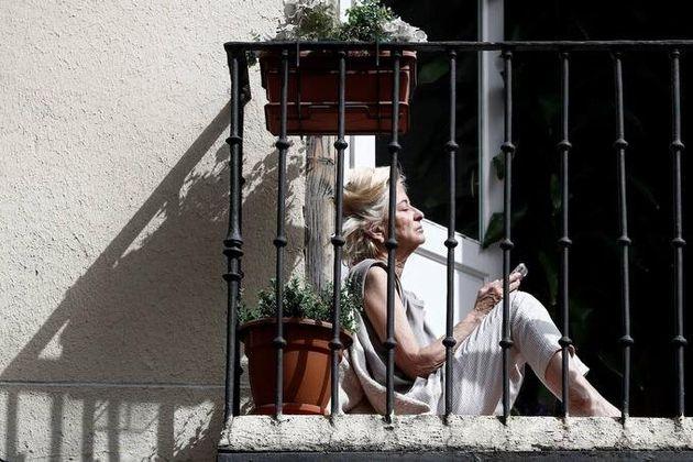 Una mujer lee y toma el sol desde su balcón durante la