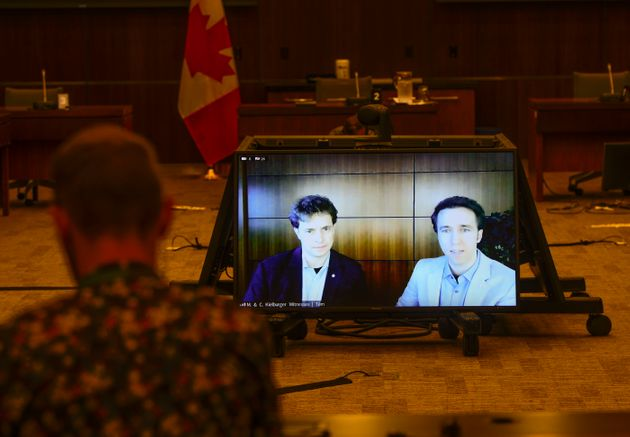 Marc Kielburger, screen left, and Craig Kielburger, screen right, appear as witnesses via videoconference...