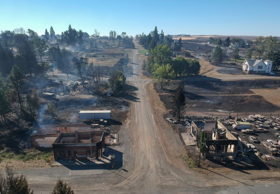 In downtown Malden, Washington, the former post office at lower left and another historic building at lower right still smolder Tuesday, a day after a fast-moving wildfire swept through the tiny town west of Rosalia.