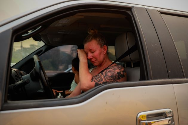 Gina Santos cries in her car after evacuating due to the LNU Lightning Complex Fire in Vacaville, California,...