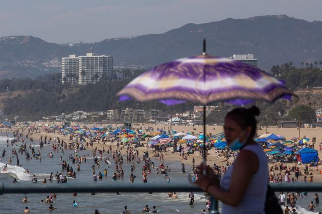 A woman uses an umbrella to protect herself from the sun at Santa Monica pier while people flocked to...