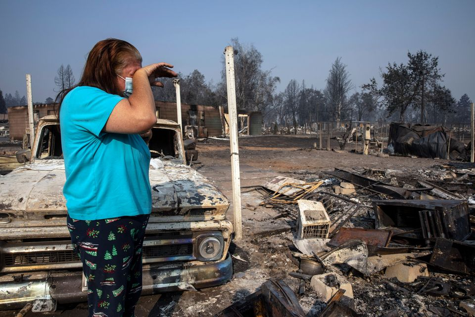 Heather Marshall stands amid what remains of her home at Coleman Creek Estates mobile home park in Phoenix, Oregon, on Thursday. The area was destroyed when a wildfire swept through on Tuesday. The Marshalls had lived at the park for 21 years.