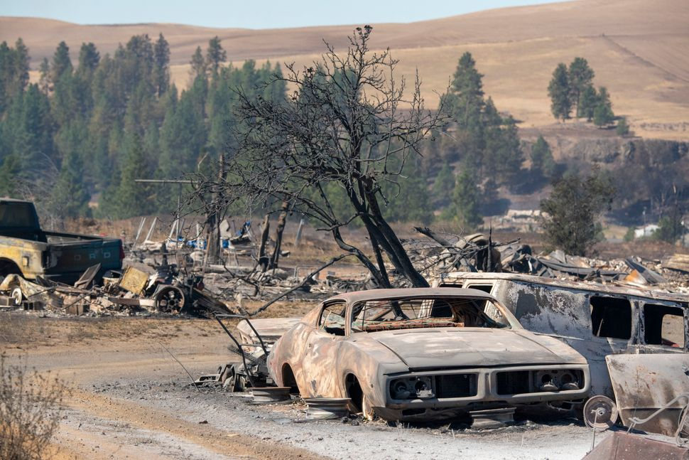 Vehicles are destroyed by a wildfire that swiftly moved through Maldin, Washington, on Tuesday.