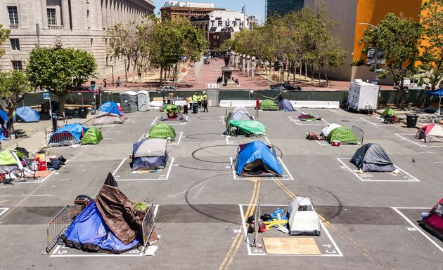 Rectangles on the ground encourage homeless people to observe social distancing at a city-sanctioned...