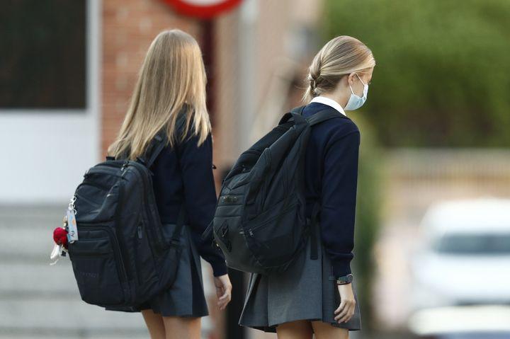 Leonor y Sofía en entrada del colegio Los Rosales cargando sus mochilas a la espalda.
