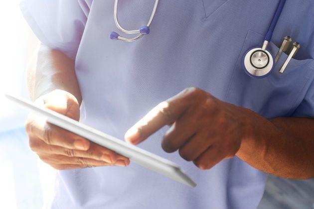 Doctor or surgeon stood in hospital ward using digital