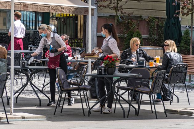 Waitresses with a mask and gloves disinfecting the table of an outdoor bar, café or restaurant, reopen...