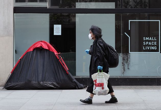A woman walking past a homeless person's tent erected outside a furniture store in Tottenham Court Road,...