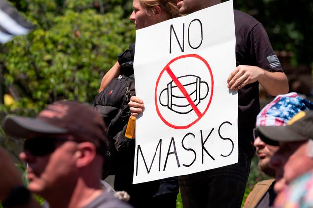 An anti-mask protester holds up a sign in front of the Ohio Statehouse during a protest in
