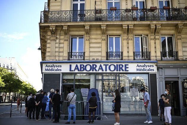 Des personnes faisant la queue pour un test PCR devant un laboratoire médical à Paris,...